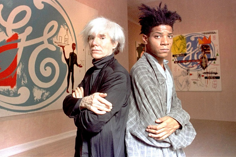 "Pop artists Andy Warhol, left, and Jean-Michel Basquiat pose in front of their collaborative paintings on display at the Tony Shafrazi Gallery in Manhattan's SoHo section, N.Y. on Sept. 24, 1985.  They  collaborated on 16 untitled canvases.  Warhol painted the company logos and Basquiat, who has roots in the graffiti movement, added dashes of color and commentary.  Warhol, working in oils for the first time since 1962, said of the collaboration: ""I just did some, and he did some.  We didn't think too much about it.  It was fun doing.""  The canvases were offered at between $50,000 and $80,000 a piece.  (AP Photo/Richard Drew)"