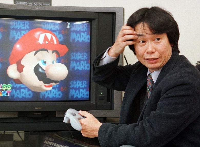 "FILE - In this Feb. 6, 1997 file photo, Shigeru Miyamoto, creator of Super Mario video game series, demonstrates Super Mario 64 in his office at the Nintendo Co. headquarters in Kyoto, Japan. Even though Mario hasn't changed much in nearly three decades, the latest game he stars in, the newly released ""The New Super Mario Bros. Wii,"" is one of the holiday season's top titles. (AP Photo/Atsushi Tsukada)"