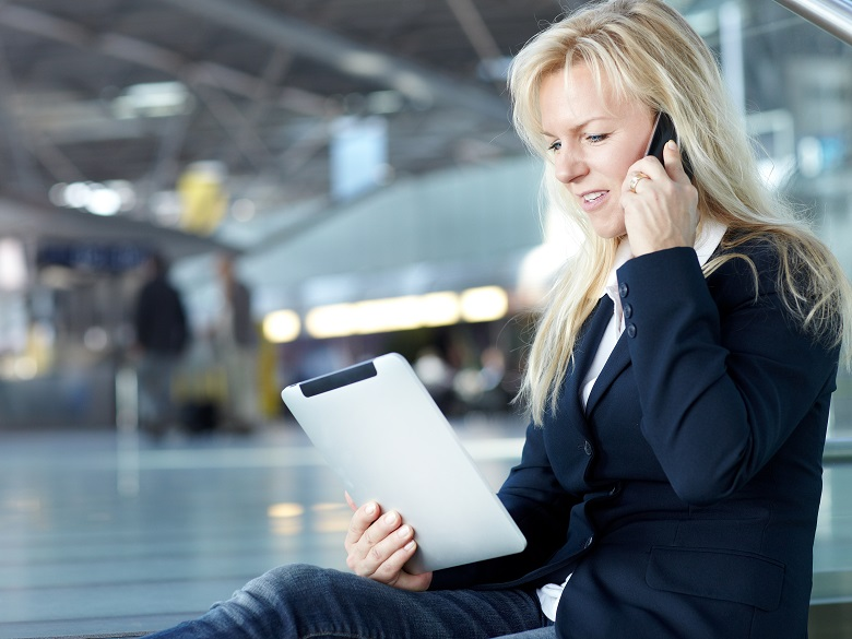 Nice buisiness women is working at the Airport with mobile Device and cellphone